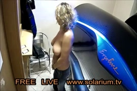 Horny milf with big tits masturbates on a bed.
